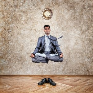 15566474-Levitation-by-Indian-businessman-in-lotus-pose-in-the-office-near-the-wall-with-clock-and-his-shoes--Stock-Photo